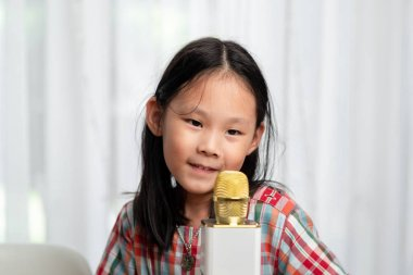 Happy Asian girl using microphone for singing at home.