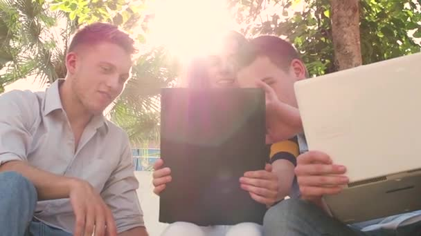 Happy university student using tablet together outside building with natural light and len flar, slow motion
