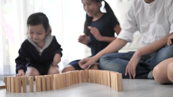 Happy Asian family playing wooden blocks together at home, slow motion.