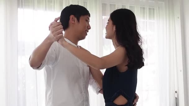 Romantic Asian couple dancing together at home, slow motion.