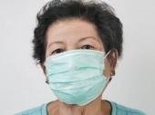 Senior Asiatin mit Ohrbügel Maske auf weißem Hintergrund.