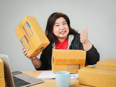 Fat Asian woman packing goods for selling online, delivery conce