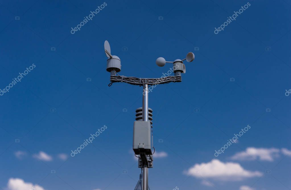 Home weather station on a background of blue sky with the sun behind the clouds. Measurement of temperature, humidity and wind direction