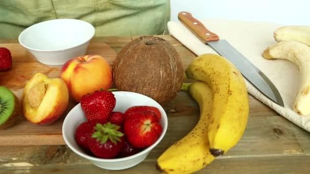 Sochory pro ovocný koktejl na řezací deska banány, jahody, broskve. Žena dává jahody v misce