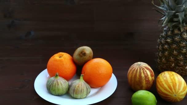 Vegetariánská strava. Na bílé plotně jsou vietnamské meloun, fíky, pomeranče, ananas.
