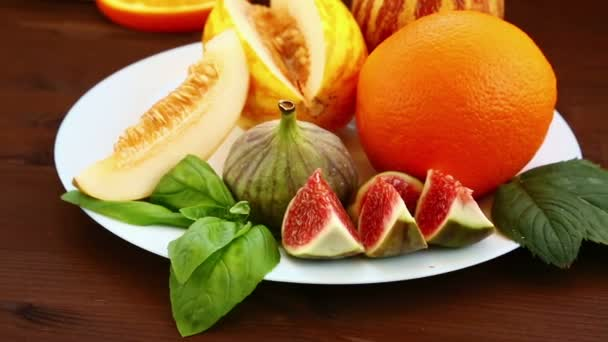 On the table lie fruit: Vietnamese melon, figs, kiwi, oranges, juice. Close-up.