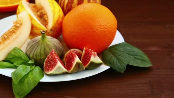 Vegetáriánus étrend. Az asztalon hazugság gyümölcs: vietnami dinnye, kiwi, füge, narancs, gyümölcslé. Közeli kép:.