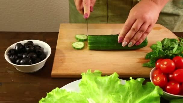 Frauenhände schneiden eine Gurke für einen Gemüsesalat.