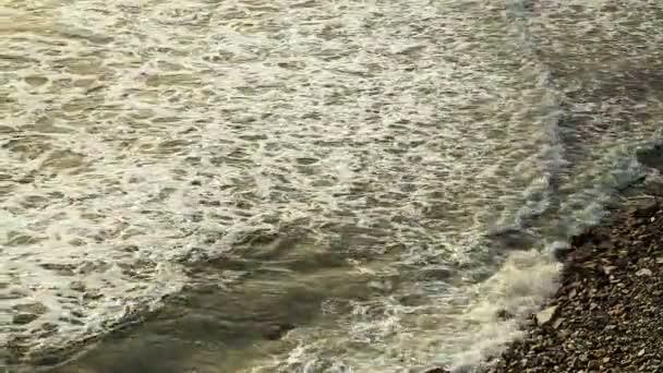 Mořské vlny s pěnou bila kamenité pobřeží