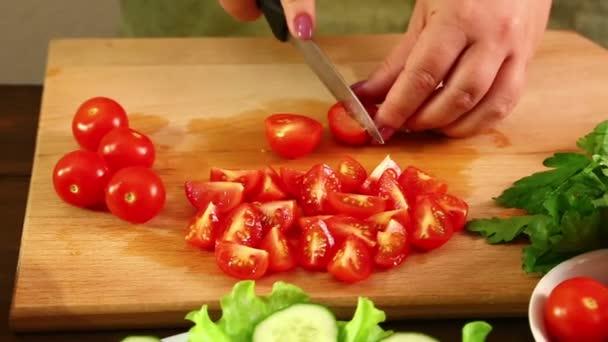 Eine Frau schneidet Kirschtomaten für einen Gemüsesalat. Nahaufnahme