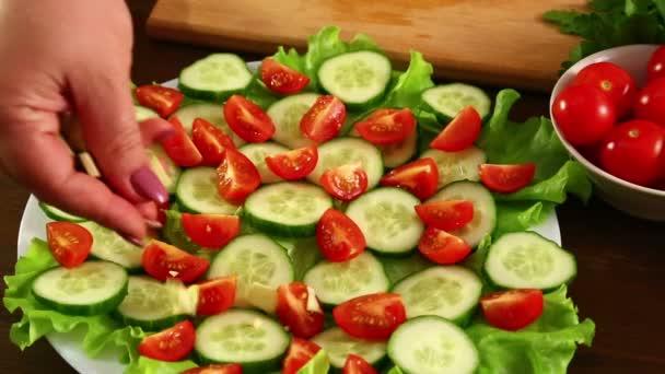 Ta přidává kousky avokáda na desku s zeleninový salát. Detail.