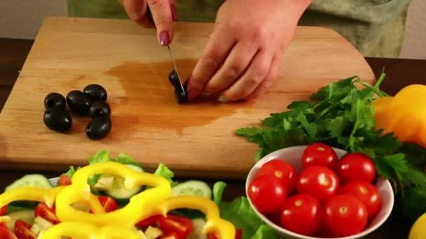 Eine Frau schneidet das Rezept in kleine Stücke schwarzer Oliven. Nahaufnahme