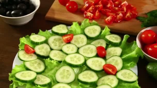 Eine Frau legt eine Tomatenscheibe auf einen Teller mit grünen Gurken. Nahaufnahme.