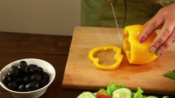 Žena řídí žlutá paprika na vaření zeleninový salát. Detail