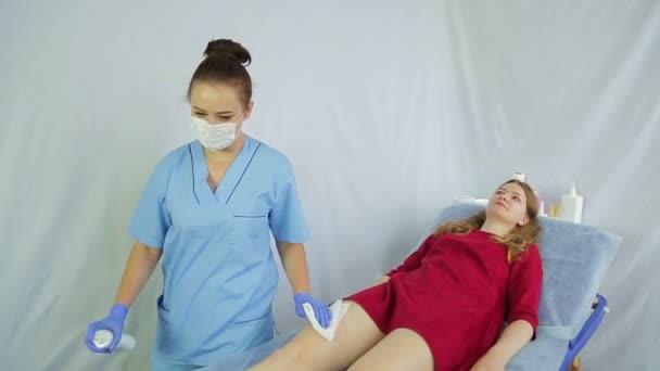 Egy fiatal nő orvos kozmetikus előkészíti a bőrt a lányok lábát a csoszogva eljárás.