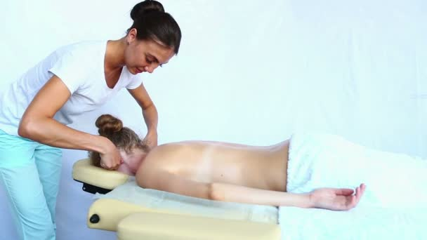 Woman - orthopedic doctor does ear massage to a young woman