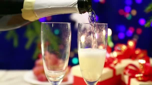 aus der Flasche wird shompanskoe in zwei Gläsern auf den Tisch mit Geschenken auf dem Hintergrund des neuen Jahres mit den Lichtern der Herlinge verschwommen Bokeh gegossen.