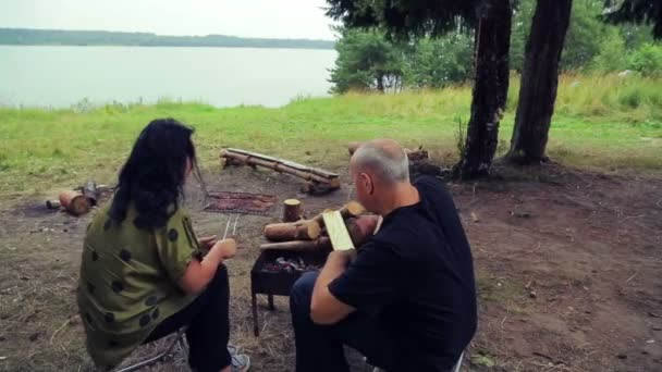 a man and a woman on the riverbank sit at the barbecue and grill fish.