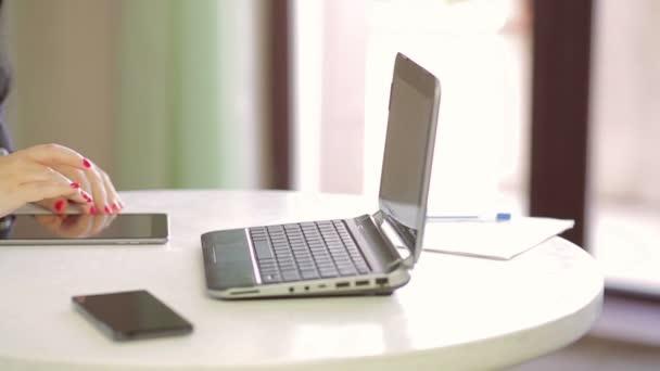 Studentka je pracovat na notebooku v kavárně a prohlížení obrázků na tabletu. Panorama z práva na lef