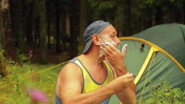 A man sits near a tourist tent and shaves his hair from his face.
