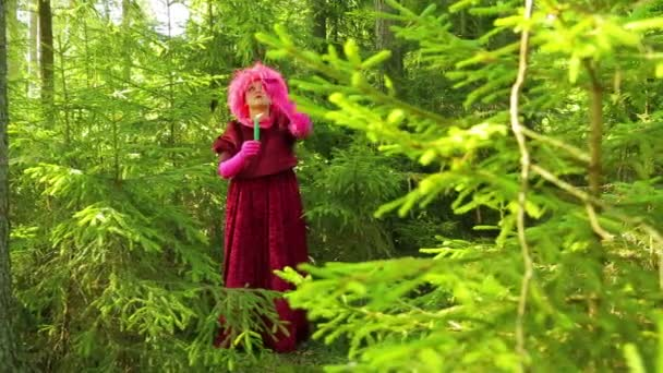 Mladé čarodějnice v smrkové lese stojí se svíčkou v ruce a přečte kouzlo.