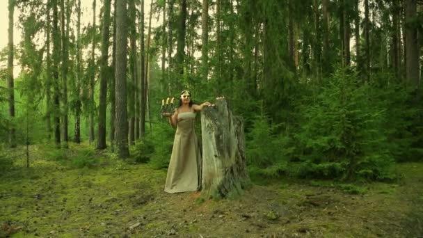 Lesní víla v Zlatou masku na tváři drží svícen se svíčkami v ruce.