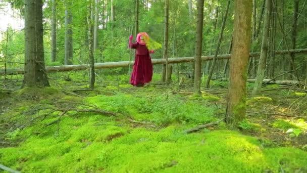 Mladé čarodějnice v lese provádí rituál s listy kapradí v slunci.