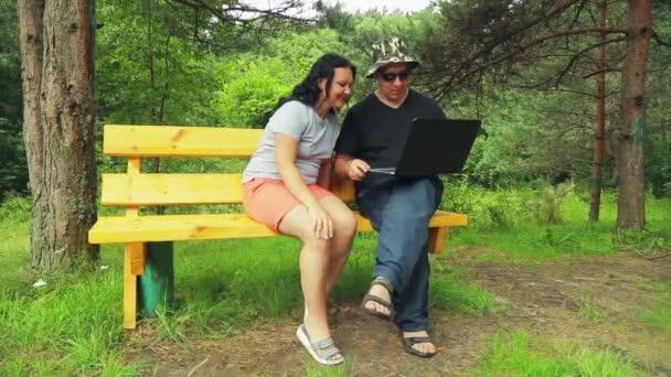 Muž a žena v parku na lavičce s notebookem číst komiksy