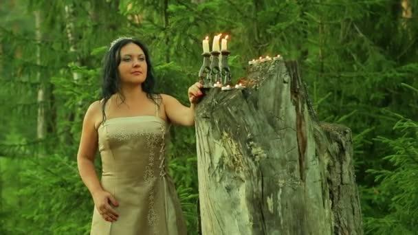 Tajemná víla v lese stojí velký pahýl se svíčkami.