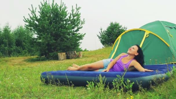 Usměvavá mladá žena leží na nafukovací matraci vedle stanu palouku v lese.
