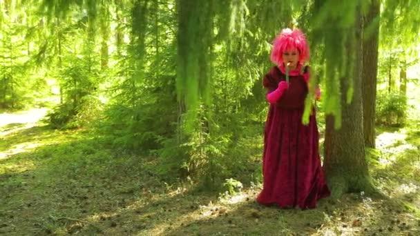eine junge Frau in Gestalt einer Hexe im Wald verzaubert eine brennende Kerze.