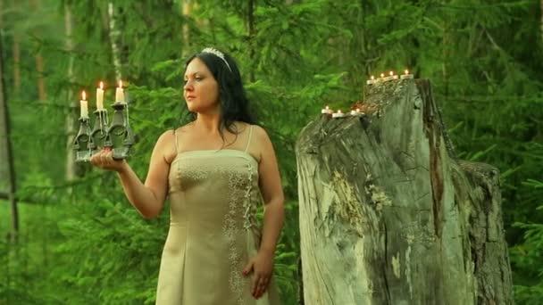 A titokzatos tündér az erdő áll egy nagy stump gyertyákkal és egy gyertyatartó égő gyertyák, a kezében tartja.