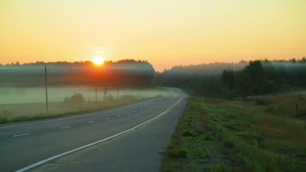 Mlha nad silnici, na které budou projíždět auta. Východ slunce. Čas kola.