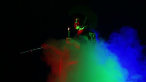 Eine junge Hexe in einem schwarzen Mantel mit einer Kerze in der Hand in einer Wolke aus Rauch.