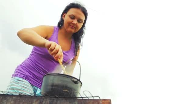 Egy nő egy kanna a tűz keverés egy leves, egy fakanállal. Átfogó terv.