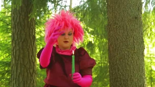 Mladé čarodějnice v lese vrhá kouzla nad hořící svíčku