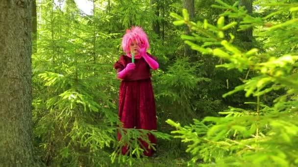 Mladé čarodějnice v lese stojí se svíčkou v ruce a přečte kouzlo.