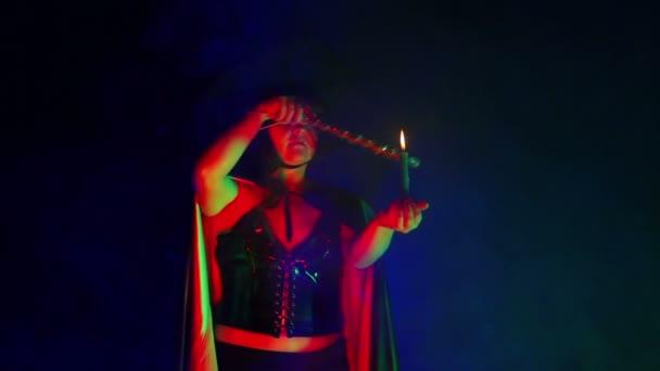 Egy fiatal boszorkány egy füstfelhő, fekete köpenyt gyertyával a kezével részt varázslat-val egy varázspálca.