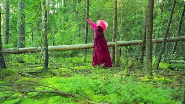 Mladé čarodějnice v červené barvě v lese bude proplétat svou holí nad hlavou.