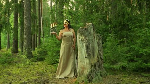 Lesní víla v zlaté masky na obličeji stojí velký pahýl a drží svícen se svíčkami v ruce.