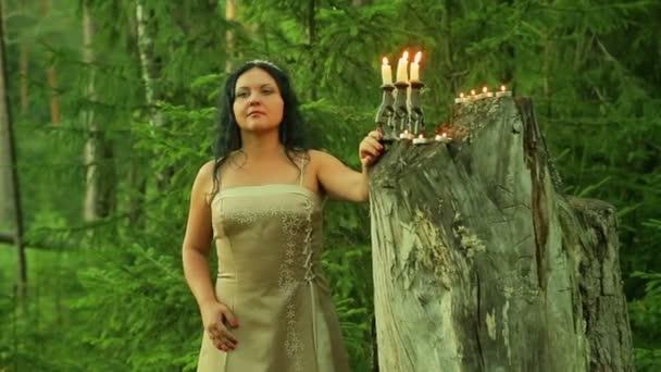 eine geheimnisvolle Fee im Wald steht an einem großen Baumstumpf mit Kerzen und schaut sich um.