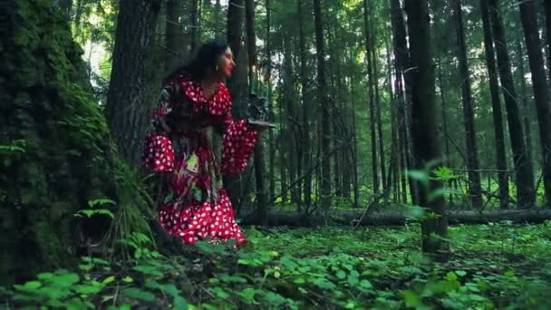mladý Cikán shuvani drží svícen s hořící svíčky a rozhlíží se schovat za strom v lesní houštiny za soumraku.