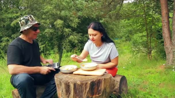 Muž a žena na okraji lesa sedět na padlé stromy a jíst ovocný salát. Muž pracuje na notebooku