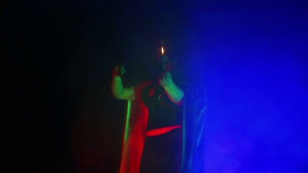 Eine junge Hexe in einem schwarzen Mantel und Hut mit einer Kerze in der Hand in einer Wolke aus Rauch.