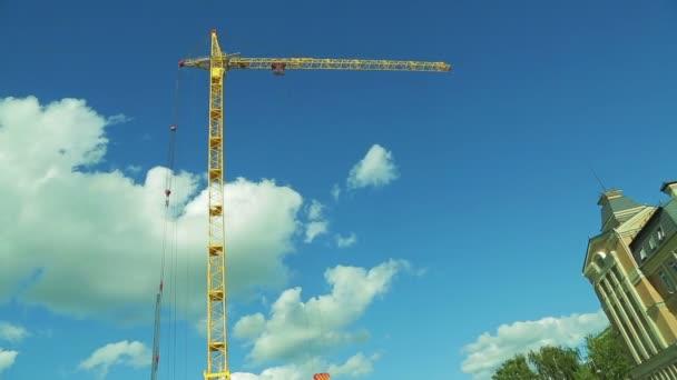 stavební věžový jeřáb, proti modré obloze s pohyblivými bílé mraky. Čas kola