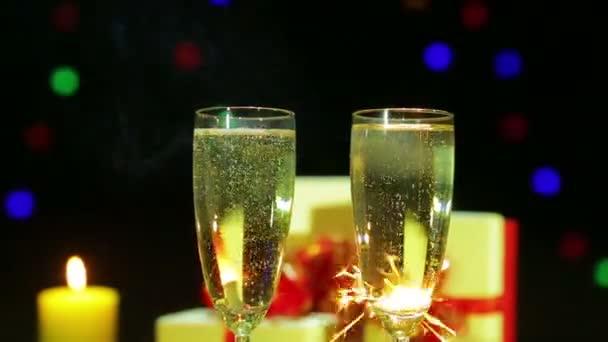 Brýle prskající šampaňského na pozadí aplikace fireworks z Bengálska světla.