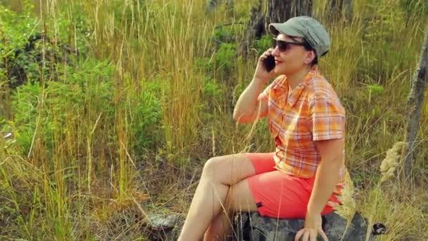 mladá žena turista v sluneční brýle a baseballovou čepici v lese za slunečného dne sedí na padlý strom a mluví o telefonu.
