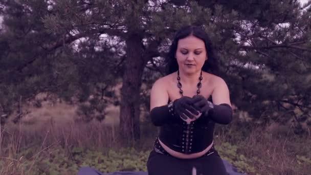 Čarodějnice v černém provede magických obřadů s pomocí rukou. Halloween