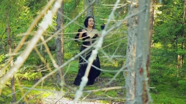 Eine Hexe Frau in schwarzer Kleidung ist einen rituellen Tanz im Wald tanzen. Halloween. Gothick Stil.