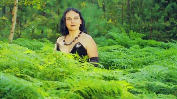 Eine lächelnde junge Hexe in schwarzer Kleidung steht in einem Wald in ein Dickicht aus Farn. Halloween. Gothick Stil.